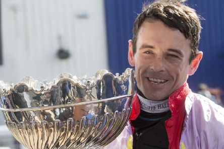 Sean Quinlan celebrates with the trophy after winning the Coral Scottish Grand National Handicap Chase onboard Takingrisks. Pic: Jeff Holmes/PA