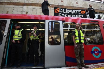 Climate activists on top of a Dockland Light Railway train at Canary Wharf station in east London. Picture: Kirsty O'Connor/PA Wire