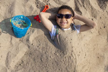 Seven-year-old Curtis Koffi is buried in sand on Broughty Ferry beach, near Dundee. Scotland has enjoyed its hottest Easter Sunday on record