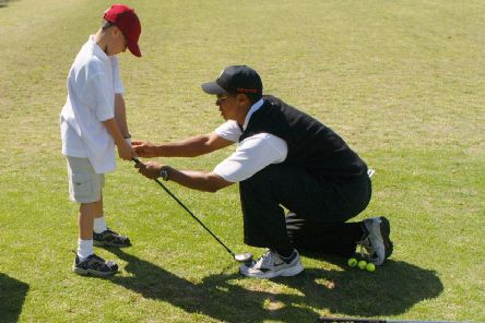 Tiger Woods teaches an eight-year-old budding golfer at his clinic. Now, following his victory in the Masters, junior sessions at clubs around the world are expected to experience a surge in youngsters taking up the sport. Picture: Getty.