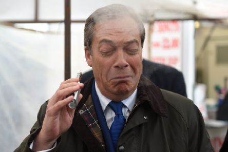 Brexit Party leader Nigel Farage coughs as he samples a Pinkman flavoured e-cigarette during a Brexit Party walkabout in Lincoln. Picture: Joe Giddens/PA Wire