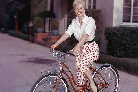 American actor Doris Day poses on a red Schwinn bicycle, late 1950s. (Photo by Hulton Archive/Getty Images)