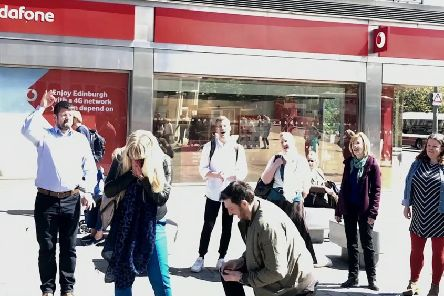 This is the heartwarming moment a man proposed to his girlfriend in the street where they first kissed. Picture: SWNS