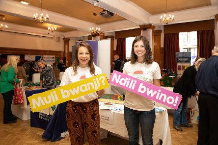 Chiara Cotronei and Nicola Goldmann, both SMP youth committee members, holding signs in Chichewa, saying . Muli Bwanji meaning 'how are you' and Ndili Bwino meaning 'I am well, thank you'. It is a very friendly greeting that you will hear used a lot in many parts in Malawi.