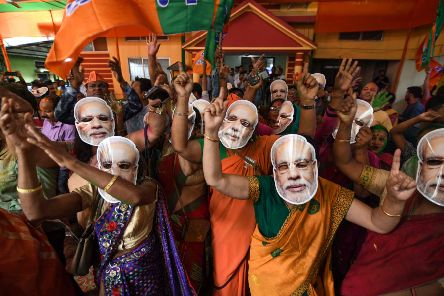 Indian Bharatiya Janata Party (BJP) supporters wearing masks of Indian Prime Minister Narendra Modi dance as they celebrate on the vote results day for India's general election. BIJU BORO/AFP/Getty Images