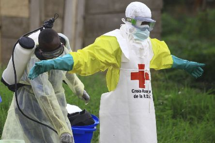 A health worker sprays disinfectant on his colleague after working at an Ebola treatment center in Beni, eastern Congo. Picture: AP Photo/Al-hadji Kudra Maliro