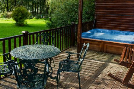 The decking and hot tub outside the french doors of the log cabin