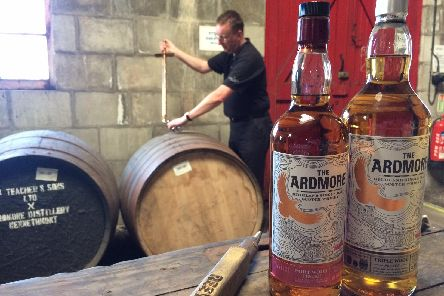 Distillery manager Alistair Longwell draws some whisky from a cask.