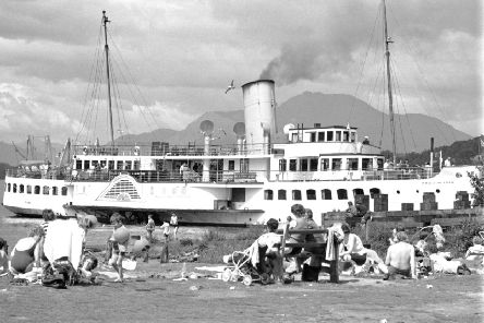 Holidaymakers enjoy the sun in Balloch as the Maid of the Loch paddle steamer passes by on Loch Lomond in July 1972