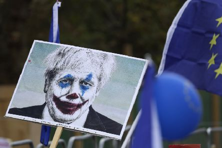 "Anti-Brexit supporters hold a placard showing current Prime Minister Boris Johnson portrayed as the Joker as they take part in a ""People's Vote"" protest march calling for another referendum on Britain's EU membership in London (Picture: Matt Dunham/AP)"