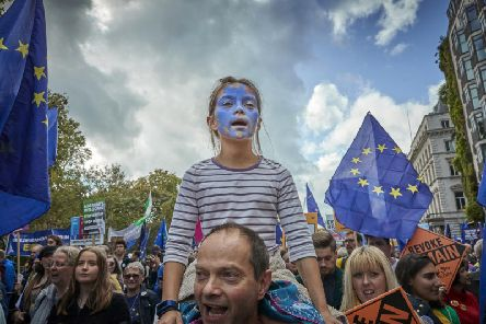 A girl sits on her father's shoulders as protesters march towards Parliament Square