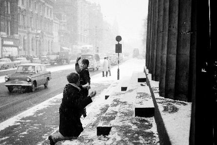 Two boys have a snowball fight outside RSA in Princes Street.