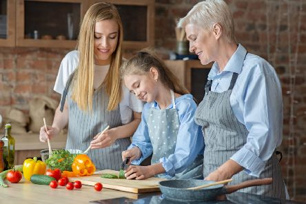 Adults teach a young girl how to cook healthy food