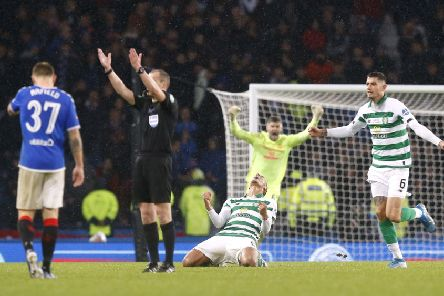 Scott Brown sinks to the turf in ecstasy as Nir Button and Fraser Forster race to join in at the final whistle. Picture: PA