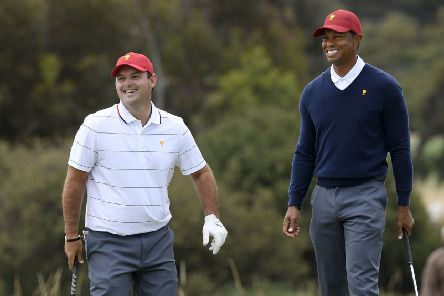 Patrick Reed, left, and US captain Tiger Woods during practice ahead of the Presidents Cup in Melbourne. Picture: Andy Brownbill/AP