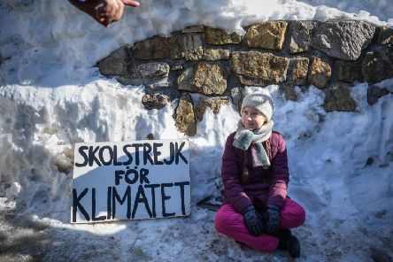 Greta Thunberg sits with a placard reading 'school strike for climate' outside the World Economic Forum's meeting in Davos in January (Picture: Fabrice Coffrini/AFP via Getty Images)