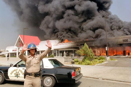 A California Highway patrolman directs raffic around a shopping mall engulfed in flames in April 1992, during the LA Riots. PIC: Carlow Chiebeck/AFP via Getty Images