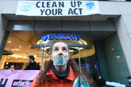 An Extinction Rebellion protester stands outside a Barclays Bank branch in Glasgow. Picture: John Devlin