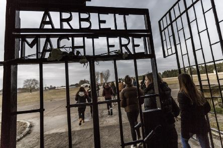 Visitors walk past the infamous entrance gate that reads: 'Arbeit macht frei' - or 'Work sets one free' - at the Sachsenhausen concentration camp memorial in Germany. (Picture: Carsten Koall/Getty Images)