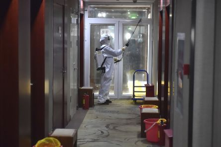 A worker in a protective suit disinfects a corridor of a Beijing hotel that has been converted to an observation and quarantine area. Picture: Chen Zhonghao/Xinhua via AP