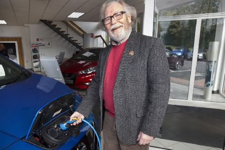 Keith Oliver charging an electric car.