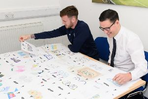 Falkirk FC's Jordan McGhee and Specsavers'  Zander McNaughton look at the entries for thjs year's family fun day competition.