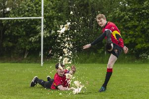 Mackie Academy FP players Cameron Pace and Jamie Lawrence smash a rugby ball cake