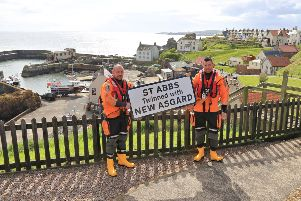 David Wilson (left) and Paul Crowe of St Abbs Lifeboat (NB NOT RNLI) with a sign marking the link between the Berwickshire coastal village and the Avengers: Endgame film, which portrays the village as 'New Asgard'