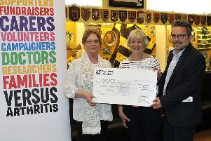 Borders branch of Versus Arthritis present a cheque