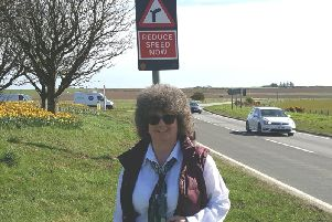 Councillor Gillian Owen next to one of the new signs at the Toll of Birness
