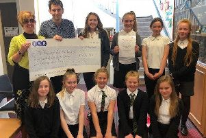 Gail McKeitch from the Ellon branch of the NAS accepts a donation from Buchanhaven School P7 pupils