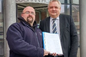 Buchan Aquatics owner Gilbert Burnett presents the petition to Buchan Area Manager Chris White