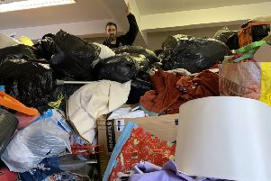 Stella's Voice staff member Bruce Robertson works his way through donations received at The Barn