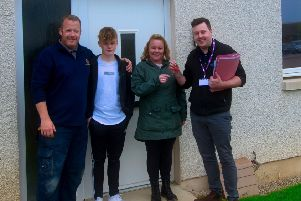 Arlene McKenzie, who moved into her new Osprey Housing Group home, with sons Adam and Cole, and partner Craig McLean, collect the keys from Peterhead Osprey Housing Officer Jamie Brown