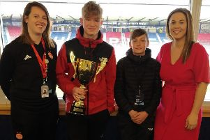 Two Peterhead Academy pupils collect the award alongside a member of the Aberdeen FC Community Trust