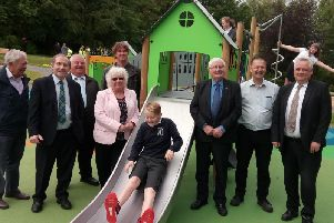A youngster tries out the new slide at Aden Country Park watched by councillors, council staff and project representatives