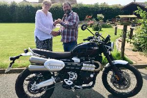 Irene is presented with her prize, a Triumph motorbike, from Teen Challenge area manager, Gordon Cruden.