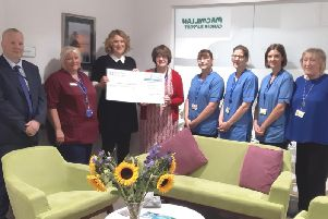 Lady Rosalind Watt hands over the cheque to oncology staff.