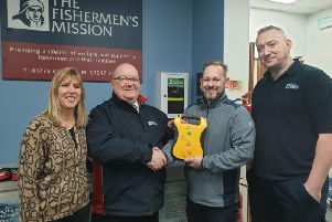 Andrew Buchan hands over the defibrillator to Superintendent Steve Murray of Peterhead Mission watched by building owner Alicia Smith and port mission officer Sandy Garvock.