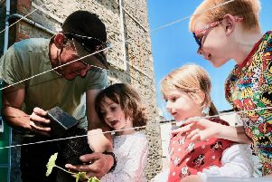 Ronnie Armstrong, Left, Head Gardener from Bute Produce planting cucumbers with Sarah, age 4 (white top), Imogen, age 3 (red top) and Lee, aged 6, Right, at Chapel Hill Community Garden. Photo by Iain Cochrane.