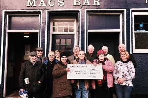 Pictured are Robert Macintyre, quiz compiler (centre) and George and Katy Ross, proprietors of  Macs Bar (far right) with some of the participants of the quiz and Jackie Telford and Lisa McConnell (holding cheque) from the Thomson Court Campus. Photo by Iain Cochrane.