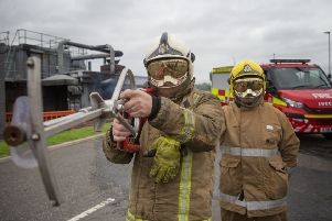 Firefighters from the Scottish Fire and Rescue Service, at their National Training Centre in Glasgow, demonstrate ultra high pressure lances, branded 'Coldcut Cobra', which will enable firefighters to blast a fire suppressant through the wall of a burning building. Pic: Jane Barlow/PA Wire