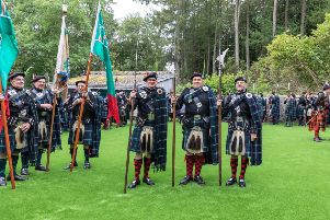 Lonach Highlanders inspect the new Astroturf during their visit