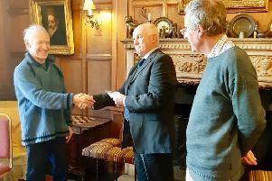 Kenny Littlejohn accepts his gift from Nick Boss, who made the presentation on behalf of the community. On the right is castle owner Andrew Bradford.