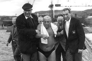 Ned Barnie is helped along Burntisland Harbour to the boat after swimming across the Firth of Forth in 1959. Picture: TSPL
