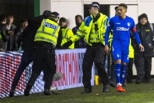 The fan is led away by police after confronting James Tavernier. Picture: SNS