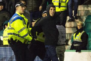 Mack being lead away by police after running onto the park and confronting James Tavernier