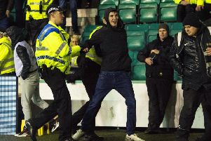 Hibs fan Cameron Mack is led away from Police after running onto the park and confronting Rangers captain James Tavernier