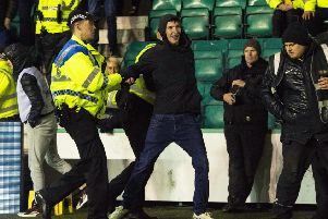Cameron Mack is led away by Police after running onto the pitch