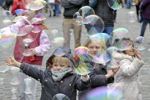 Children play with bubbles on the road during the Open Streets event earlier this month. Picture: Neil Hanna